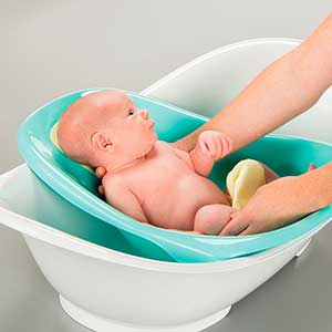 baby being washed in convertible baby bathtub