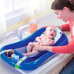 Mom cleaning baby in hammock baby bathtub