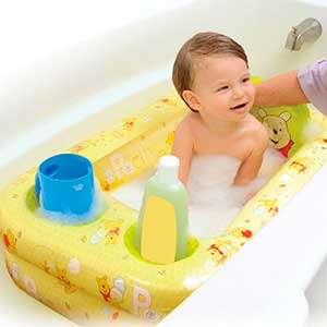 baby being washed in an inflatable baby bathtub